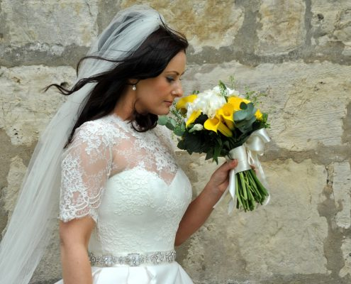 Bride smelling her bouquet with natural hair and make-up